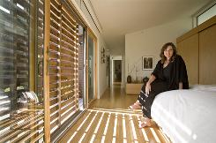 "Michelle Kaufmann sits in the bedroom of the green, modular home she designed and built. ""We have tons of work,"" she says, but still she'se begun to close her eco-design firm because her clients can't get financing and two factory partners went out of business."