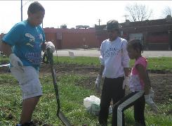 David Smith, left, his mother, Earlean White, center, and her daughter Katherine White pull weeds on a berm that will surround an urban garden near White's home in Detroit.