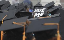 "A cap worn by graduate Paul Szeto, of Cambridge, Mass., reads, ""Hire Me"" as graduates listens to speakers during the May 29 commencement at the University of Massachusetts-Boston, which graduates 35%."