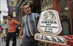 "A souvenir shop owner in Cairo displays a metal plaque comparing Obama with the pharaoh Tutankhamen. Hieroglyphics at base of plaque were claimed by the vendor to spell the name ""Obama."""