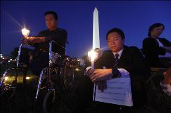 Former Chinese student protesters Fang Zheng, left, and Wang Dan attend a candlelight vigil near the Washington Monument on May 30 to honor victims of the 1989 massacre at Tiananmen Square.
