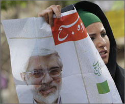 A supporter of presidential candidate Mir Hossein Mousavi distributes his posters in Tehran.