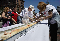People work to prepare a gigantic lobster roll in an attempt to set a Guinness World Record during the Old Port Fest in Portland, Maine.