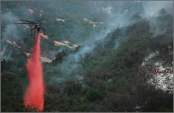 With a crew working at right, a firefighting helicopter drops a load of fire retardant on smoldering hot spots in Santa Barbara, Calif.