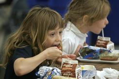 Kindergartners Ashlie Cleyman, 6, left, and Alleyah Hickman, 6, eat lunch Monday at school. All the kids at Daniel Webster School 46 in Indianapolis get free lunches.