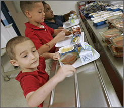 Thomas Young, 6, gets his lunch at school on June 8. At this Indianapolis school, 100% of the kids get free or reduced- price lunches.