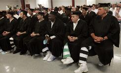Wearing striped uniforms beneath their gowns, 28 inmates at the Mississippi State Penitentiary listen to Charles Kelley, president of the New Orleans Baptist Theological Seminary, prior to receiving their associate and bachelor of arts degrees from the seminary's Christian ministry program in Parchman, Miss.