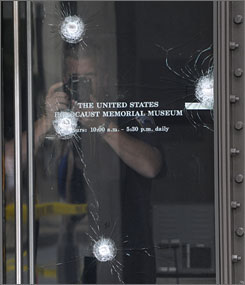 An investigator photographs bullet holes in the door of the Holocaust Museum in D.C. Thursday, a day after a security guard was shot and killed there.