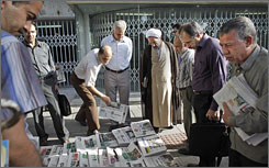 Iranians stop to look at the morning's newspapers at a street kiosk in Tehran on Saturday. 