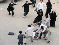An Iranian supporter of defeated presidential candidate Mir Hossein Mousavi is beaten by government security members as fellow supporters come to his aid during riots in Tehran, Iran, on Sunday.