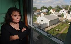 "All the homes visible from the second-floor bathroom of Linda Seger's Cedar Rapids home are vacant and probably will be razed. Seger and her husband rebuilt after severe flooding in Iowa last June. Says Linda: ""I would like to see life again."""