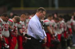 Pleasure Ridge Park High School football coach David Jason Stinson, shown in January during a moment of silence for sophomore Max Gilpin, has been released from teaching duties pending the outcome of his trial on charges of reckless homicide. Max collapsed during summer practice at the Louisville school.