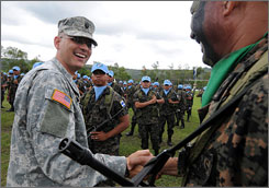 A U.S. servicemember says goodbye to a Honduran soldier June 8 in Tegucigalpa. The Honduran unit was bound for Lebanon on a U.N. peacekeeping mission.
