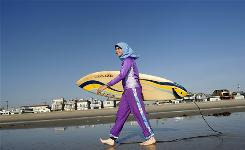 Dressed in swimwear designed for Muslim women, Sama Wareh walks along the sand in Newport Beach, Calif.