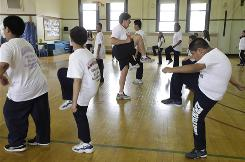 Betty Hale, center, instructs a physical education class in a 100-year-old gymnasium at Eberhart Elementary School in Chicago. To fight obesity, kids and their parents should have access to school playing fields and athletic facilities even when schools are closed, some argue.
