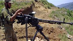 A Pakistani soldier stands with his heavy machine gun on a hill of the Biha valley in upper Swat on Saturday where the military launched an operation against Taliban militants.