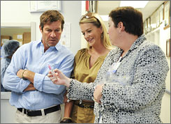 Dennis Quaid, left, and his wife, Kimberly Buffington, center, tour the Children's Medical Center in Dallas in July 2008. The Quaids, whose twins were given an overdose of a blood thinner as newborns at a California hospital, were there to learn about a system to prevent such errors.