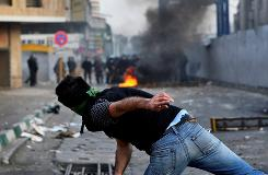 A demonstrator hurls a projectile at riot police Saturday in Tehran, Iran. State media reported that 10 people died in clashes Saturday. The capital's streets were mostly quiet Sunday.