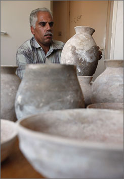 A representative of the Palestinian Ministry of Tourism examines pottery found recently during renovation of a home in Bethlehem, the place of Christ's birth, in the West Bank.