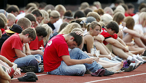 High school students react during a vigil for Aplington-Parkersburg High School football coach Ed Thomas on Wednesday in Parkersburg, Iowa. A gunman shot Thomas in the school's weight room early Wednesday morning.