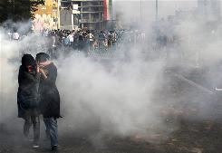 Two women take cover during one of several anti-government protests in Tehran, Iran, on Saturday.