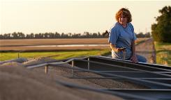 Gayla Moeckel inspects freshly cut wheat on her farm near Plevna, Kan. Moeckel left her teaching job in 2004  and lost the health insurance that went along with it. She must now pay for preventive procedures with her own money.