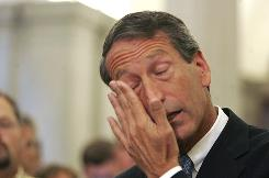 South Carolina Gov. Mark Sanford wipes his tears as he admitted to having an affair during a news conference in Columbia, S.C., on Wednesday. Sanford said he is resigning as chairman of the Republican Governors Association.