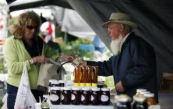 Peggy Hunter of Sterling Heights, Mich., buys jam from Lonnie Yoder on June 11 at the Shipshewana Flea Market in Indiana.