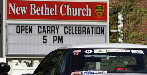 A car displaying pro-gun stickers enters the lot of the New Bethel Church by a sign advertising an event in which the church allowed hanguns to celebrate the Second Amendment in Louisville, Ky.