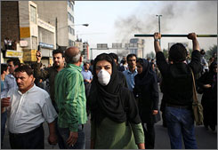 An Iranian woman wears a mask amid fires in the streets of Tehran on Saturday as crowds protested the re-election of President Mahmoud Ahmadinejad.