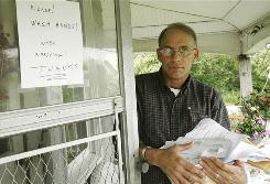 Carpenter Greg Douglas opens the door to his home, holding dozens of medical bills, in Harpswell, Maine. A sign on the door asks visitors to wash hands because his immune system was compromised after an accident.