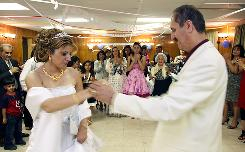 Family and friends surround Dunia Majdob and husband Nadher Majdob as they dance at their wedding reception at the Mandaean Association of Michigan Hall in Ferndale, Mich., June 26.