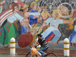 """A mural shows townspeople lighting kegs of gunpowder, fireworks and """"castillos,"""" or scaffolds covered with pyrotechnics, in Tultepec, Mexico."""
