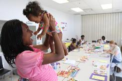 Expectant mother Keishawn Williams, 22, plays with Sia Rosalia Ahmadu, 8 months, at the Family Health and Birthing Center in Washington, D.C. Williams, a peer counselor and mother of two, helps educate local women about breastfeeding.