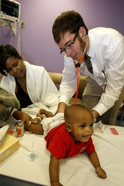 Dr. Max Rohrbaugh examines 6-month-old Riley Matthews as his mother Kenya Matthews, watches in the emergency ward at Children's Hospital in Pittsburgh. It can take days for the results of diagnostic tests to wind up in a hospital's paper chart, while only hours later, Riley's test results and long note from a lung specialist popped up in his digital chart.
