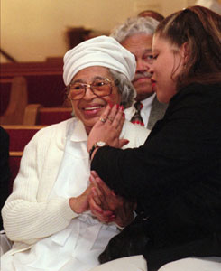 Civil rights pioneer Rosa Parks, then 85, smiles as her neice, Shelia Keys, touches her face while they talk in a front row pew before services at St. Matthew AME Church in Detroit on June 7, 1998.