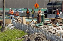 Workers take a break at a construction site along Interstate 294 near Chicago on June 1. Public construction projects may increase in coming months driven by stimulus spending.