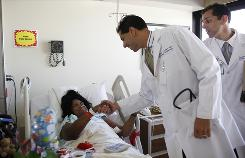 Doctor Rainer Khetan shakes hands with patient Moleta McDonald, 40, of Dallas, Texas, as his twin brother, Roger Khetan, looks on at Baylor Hospital, which has the lowest rate in the country of heart failure readmission.