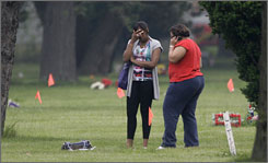 Family members search for the graves of relatives at Burr Oak Cemetery in Alsip, Ill. on Friday. Orange flags mark possible burial sites that may have been disturbed.