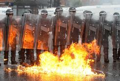 Police stand back from burning fuel in Belfast on Monday, where riots broke out in protest of a parade by a major Protestant brotherhood.
