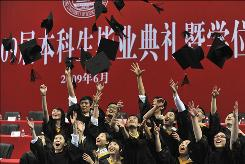 Graduates throw their mortarboards during a ceremony at a university in Wuhan, China, on June 24.