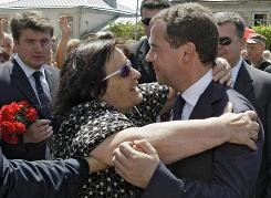 A woman hugs Russian President Dmitry Medvedev, right, during his visit to the South Ossetia region of Georgia on Monday. -