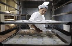 Carlos Pereira works at his bakery in Las Vegas. Pereira's wife, Kathia, helped draft a bill that reduces the liability of businesses that give foods to charities.  