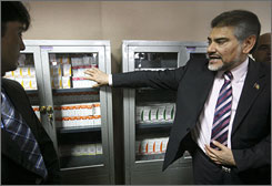 Afghan Health Minister Sayed Fatimie, right, explains HIV/AIDS medicines at a treatment center in Kabul on April 21.