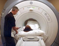Jason Scherer positions a patient for an MRI scan last month at Front Range Orthopedics in Longmont, Colo. Proponents of a plan to reduce funding for MRIs say the exams are overused.