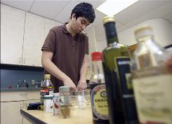 Louis Cholden-Brown prepares to cook a meal in his dorm at Columbia University in New York.