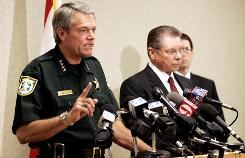 Escambia Sheriff David Morgan stands with State Attorney Bill Eddins and Assistant State Attorney Greg Marcille during a press conference in Pensacola, Fla,. on Thursday. Eddins said investigators also found several guns.