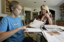 Kerry Dickinson sits with her son, Sam, 13, while he does his eighth-grade math homework at their home in Danville, Calif.