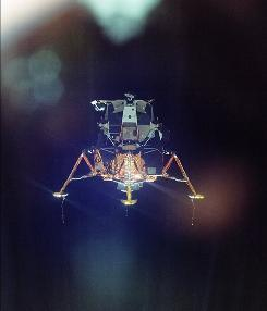 "In this July 20, 1969 photo provided by NASA and taken by Lt. Michael Collins through the window of the lunar command module, the Apollo 11 lunar module decends to the surface of the moon carrying astronauts Neil Armstong and Edwin ""Buzz"" Aldrin."