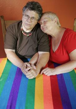 Judy Rickard, left, sits at a dining room table with her partner, Karin Bogliolo, a citizen of Great Britain who is only able to stay in the United States for six months at a time.